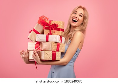 Excited pretty blonde lady in dress holding stack of gift boxes over pink studio background. Celebrating Woman's Day, Valentine's, birthday, anniversary. Shopping for holiday concept