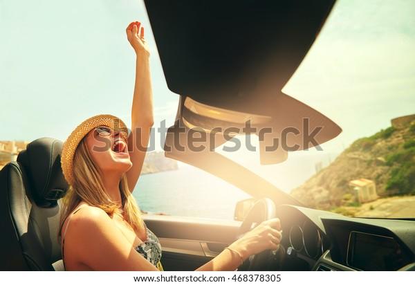 Mujer linda emocionada con sombrero y gafas de sol que llega a su puño en el aire como si celebrara en un automóvil convertible de alto nivel