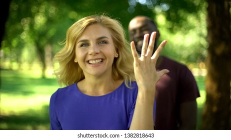 Excited pretty woman showing engagement ring, interracial marriage, happiness