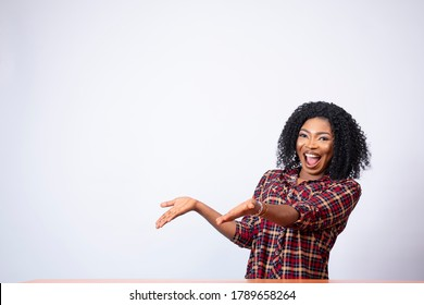 an excited pretty young african woman sitting at a desk, happy and gestures to the space on her side