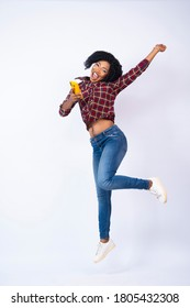 excited pretty young black lady holding her phone jumps in excitement