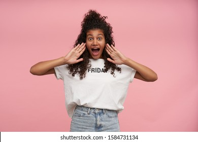 Excited pretty young curly long haired brunette woman with dark skin raising palms to her mouth and looking at camera with wide eyes and mouth opened, isolated over pink background