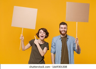 Excited protesting two people guy girl pointing index finger on protest signs broadsheet blank placard on stick isolated on yellow background. Protests strikes pickets concept. Youth against city