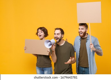 Excited protesting young people guys girl hold protest signs broadsheet blank placard on stick scream in megaphone isolated on yellow background. Protests strikes picket concept. Youth against city