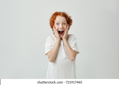 Excited redhead boy with freckles holding face with hands, with happy expression and opened mouth after parents gave him sweets.