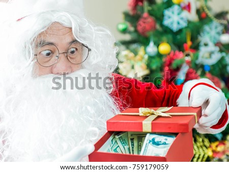 7689e708671eb Excited Santa Claus hold money in preparation to give to you for Christmas  or the concept