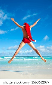 Excited Santa with extra long hat jumping in skimpy red speedos on the shore of a beach in a tropical holiday celebration