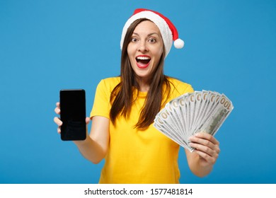 Excited Santa girl in Christmas hat posing isolated on blue wall background. New Year 2020 celebration holiday concept. Mock up copy space. Hold fan of cash money mobile phone with blank empty screen
