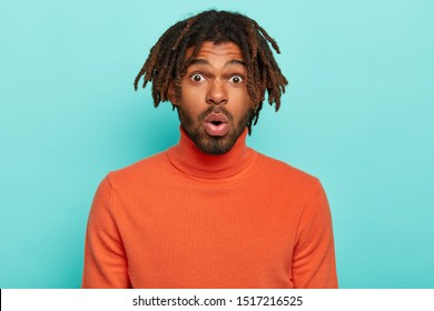 Excited scared dark skinned Afro man with dreadlocks, wears orange turtleneck, keeps mouth opened, reacts on shocking news from interlocutor, poses against blue background. People, fear, astonishment