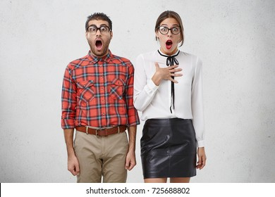 Excited scared nervous unshaven man and woman look with widely opened mouth into camera, stand side by side, have eyes full in disbelief. Funny surprised couple see something strange and scared