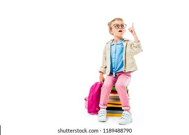 excited schoolchild pointing up and having idea while sitting on pile of books with backpack isolated on white, studying concept