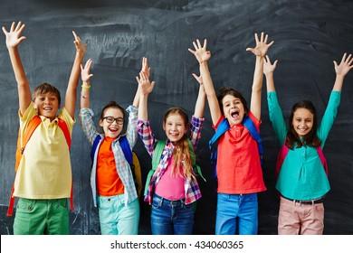 Excited schoolchildren standing with hands up