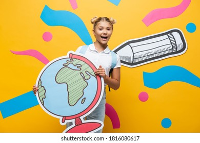 excited schoolgirl holding globe maquette and looking at camera on yellow background with paper pencil and colorful elements