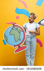 excited schoolgirl pointing with finger at globe maquette near paper cut pencil and colorful elements on yellow