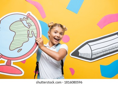 excited schoolkid holding globe maquette near abstract elements and paper cut pencil on yellow