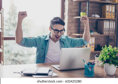 Excited screaming young man looking at the screen of his computer and triumphing with raised hands