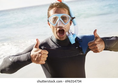 Excited scuba guy in wetsuit, mask and snorkel, thumbs up