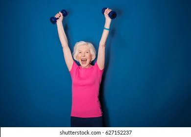 Excited senior fitness woman training with dumbbells isolated on blue