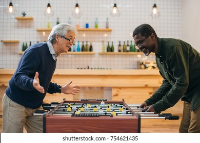 excited senior friends playing table football at bar