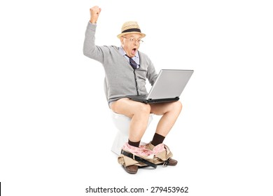 Excited senior gesturing happiness seated on a toilet and working on a laptop isolated on white background