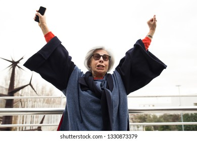Excited senior lady with smartphone celebrating success. Grey haired mature woman in sunglasses and overcoat throwing hands in air and enjoying win. Success gesture concept