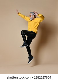 Excited senior millionaire man dancing jumping in yellow sunglasses hands up fashionable men senior on beige background