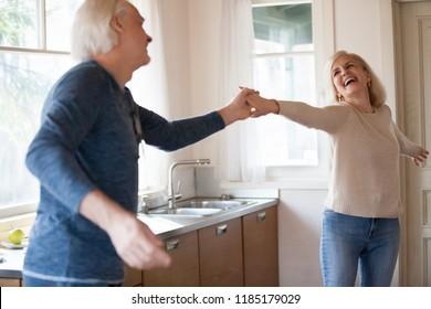 Excited senior woman dancing with mature loving husband in kitchen, old married healthy couple laughing holding hands having fun cooking, active happy middle aged elderly family at home lifestyle