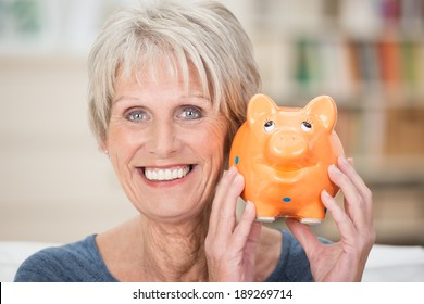 Excited senior woman holding up her piggy bank smiling in anticipation of a planned vacation or purchase to be paid for from her nest egg and savings