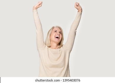 Excited senior woman raised stretched hands open mouth laughing screaming with joy feels happy isolated on grey studio background, weekend no stress euphoric lucky lady celebrating lottery win concept