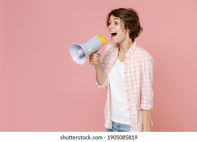 Excited shocked cheerful funny young brunette woman 20s wearing casual basic checkered shirt standing screaming in megaphone looking aside isolated on pastel pink colour background, studio portrait