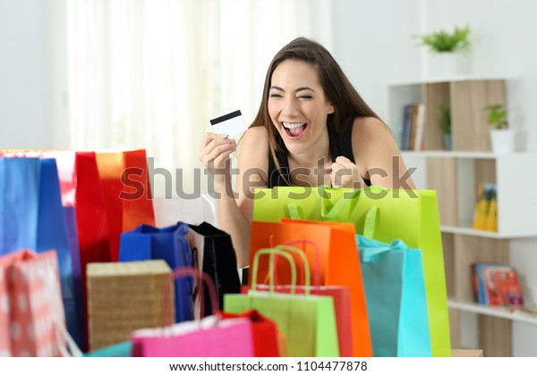Excited shopper looking at multiple purchases in colorful shopping bags at home