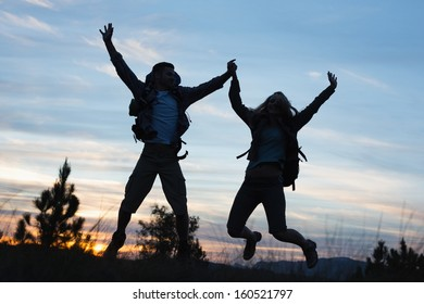 Excited silhouette couple holding hands and jumping against the sky at dusk