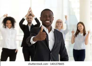Excited smiling African American leader, employee or manager show thumbs up, satisfied client pleased with service, happy boss supported by diverse cheering colleagues, celebrating business success