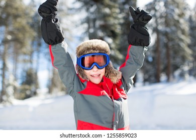 excited smiling boy in ski goggles ready for sledding, enjoying winter fun activities