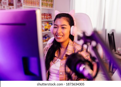 Excited and smiling gamer girl in cute headset with a mic playing an online video game and live streaming. Young Asian woman talking to players and audience on computer in neon led light room at home