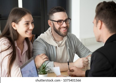 Excited smiling millennial couple discussing mortgage loan investment or real estate purchase with realtor, happy young clients customers being consulted by financial advisor, broker or architect