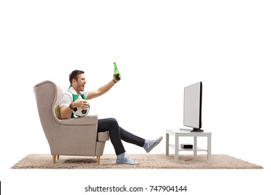 Excited soccer fan watching football on television and having a beer isolated on white background
