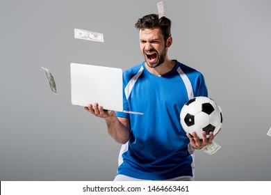 excited soccer player with ball and laptop near falling money on grey