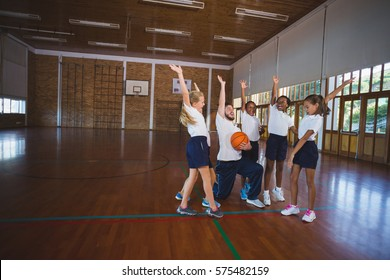 Excited sports teacher and school kids playing in basketball court at school gym