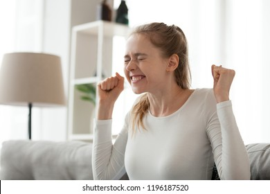 Excited student sitting on couch at home passed examination or getting scholarship. Happy girl with closed eyes feels great getting good post hired received date invitation or dream came true concept