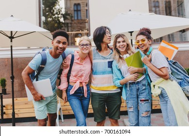 Excited students posing together in front of outdoor cafe, holding folders and laptops. Portrait of cheerful friends going to celebrate successful passing of exams.