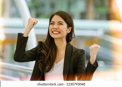 Excited successful business woman smiling and raised hands up celebrate with happily , successful winner businesswoman with fists up, keep fighting, You can do it concept.