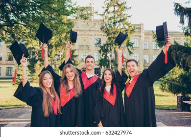 excited  successful happy five graduates in robes together rise mortar-board with tassel