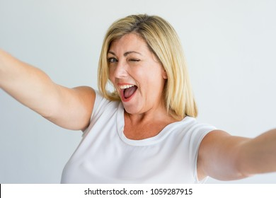Excited successful lady winking at camera while taking selfie. Cheerful enigmatic woman posing for camera. Ecstatic concept
