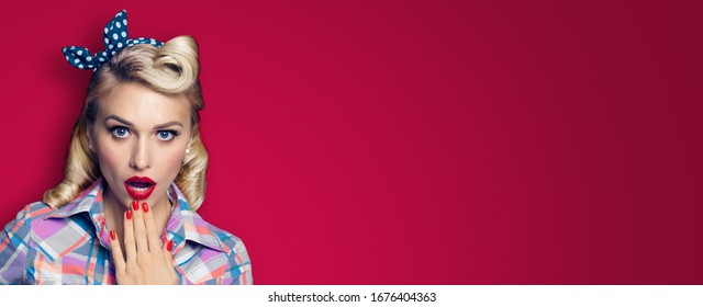 Excited surprised blond woman. Girl pin up with open mouth. Retro and vintage concept. Dark red color background. Copy space for some text. Wide horizontal banner composition.