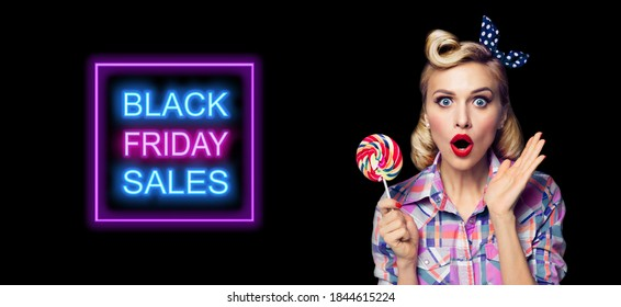 Excited surprised pinup woman with lollipop. Girl pin up with open mouth. Blond model at retro fashion and vintage concept. Dark background. Black Friday sales neon light sign.