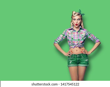 Excited surprised woman. Girl in pin up style, looking sideways. Blond model at retro fashion and vintage concept. Green color background. Copy space for some advertise slogan, imaginary or text.