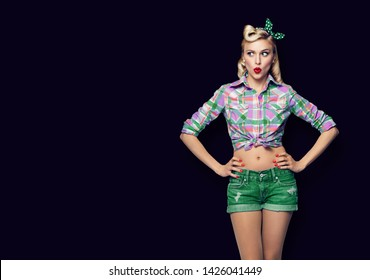 Excited surprised woman. Girl in pin up style, looking sideways. Blond model at retro fashion and vintage concept. Black color background. Copy space for some advertise slogan, imaginary or text.