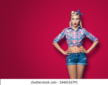 Excited surprised woman. Girl in pin up style, looking sideways. Blond model at retro fashion and vintage concept. Dark red color background. Copy space for some advertise slogan, imaginary or text.