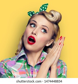 Excited surprised woman. Girl in pin up style, looking sideways. Blond model at retro fashion and vintage concept. Yellow color studio background. Square composition.